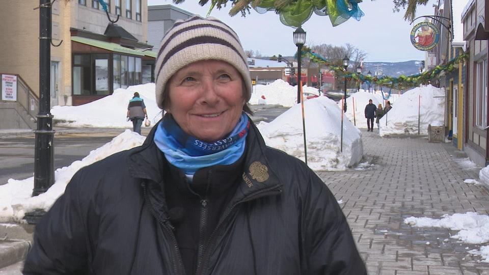 Claudine Roy debout dehors dans une rue commerciale en hiver.