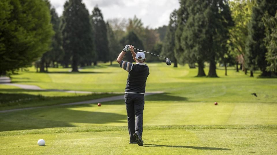 Un golfeur de dos sur un tertre de départ