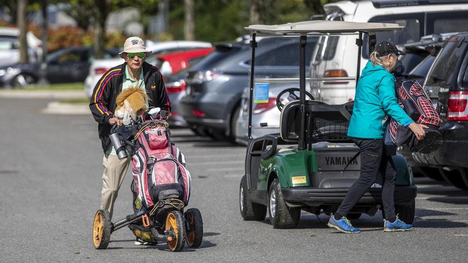 Des golfeurs se préparent dans un stationnement.