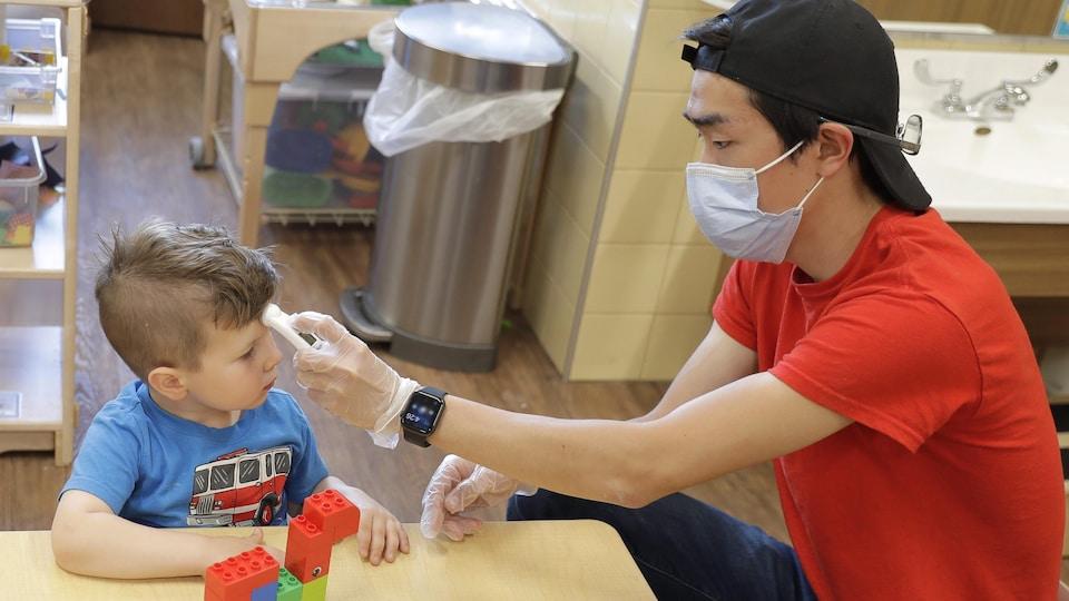 Un éducateur prend la température d'un enfant dans une garderie.