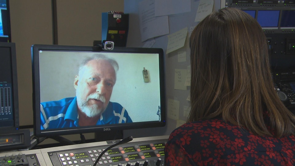 Un homme sur un écran parle à une journaliste qu'on voit de dos.