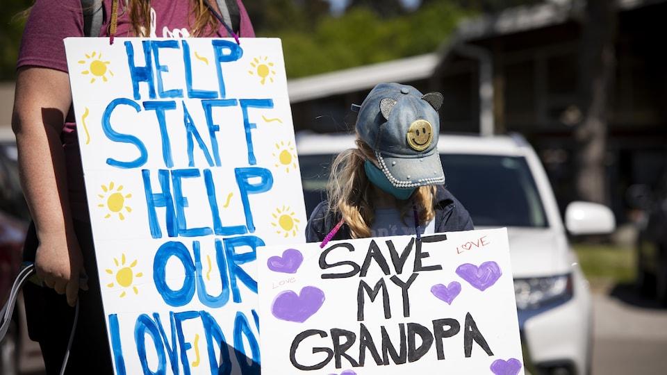 Une fillette et une femme portant des couvre-visages brandissent des pancartes sur lesquelles on peut lire «Help staff, help our loved ones» et «Save my grandpa».
