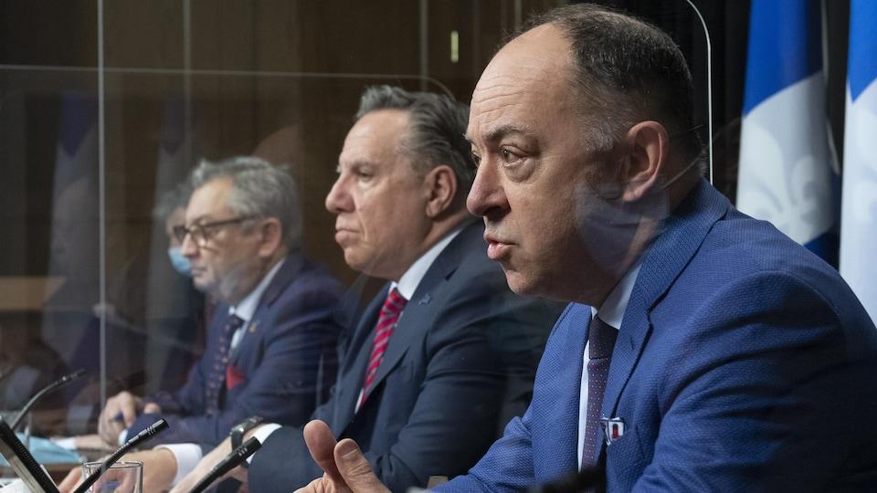 Les trois hommes sont assis côte à côte, séparés par des plexiglas.