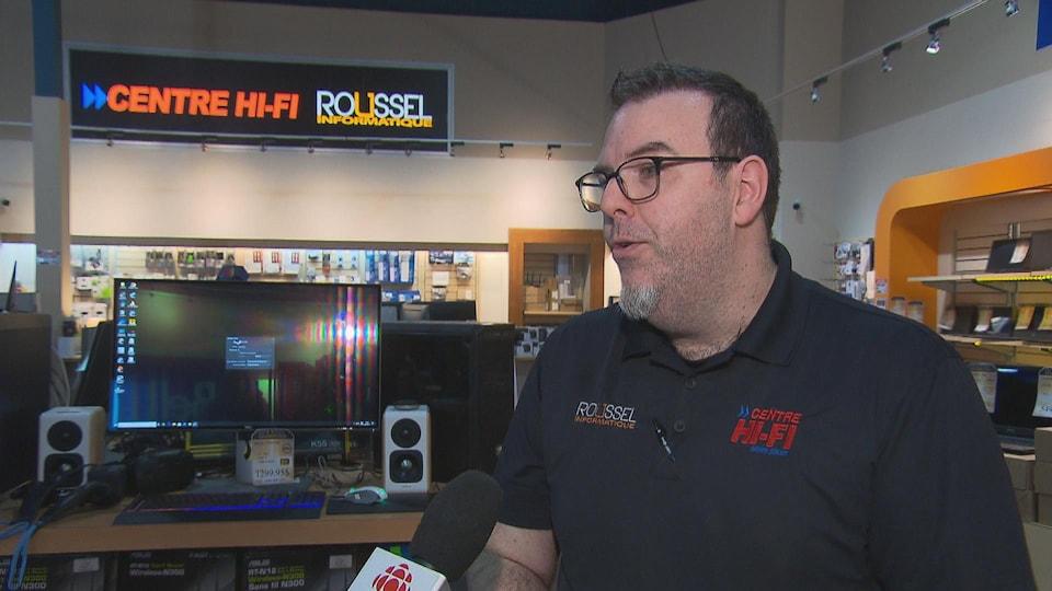 Un homme interviewé dans un magasin d'informatique.