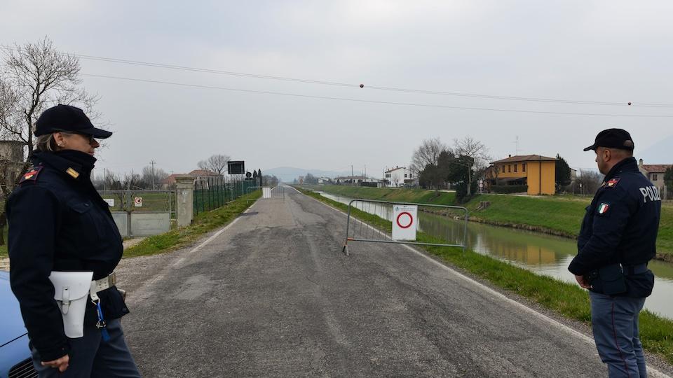 Des policiers italiens contrôlent l'entrée du village de Vo'Euganeo en raison de l'éclosion de la COVID-19, près de Venise, en Italie.