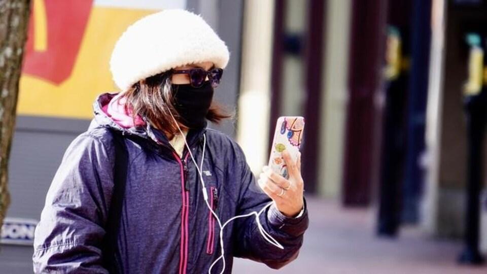 Une femme portant un masque parle au téléphone.
