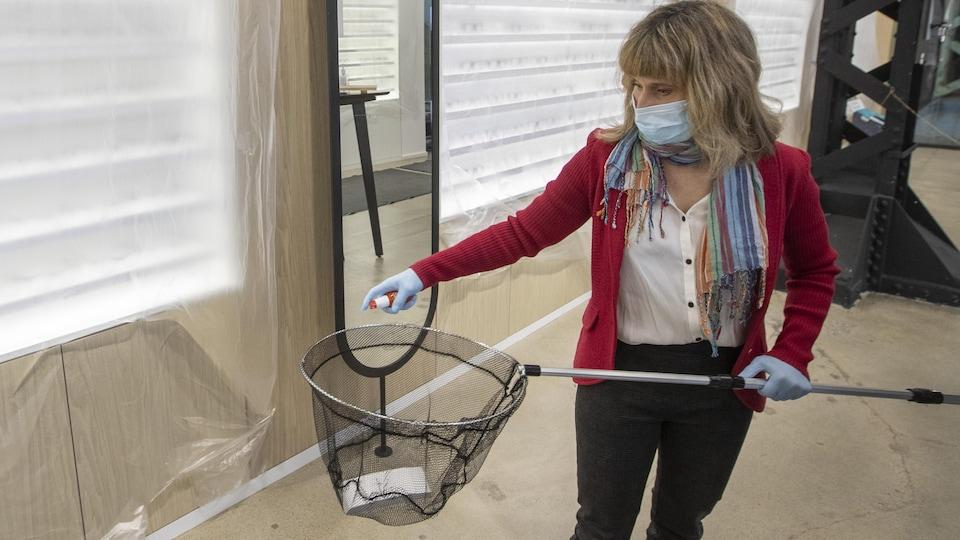 Une femme portant un masque de protection et des gants de caoutchouc désinfecte un filet à pêche dans une clinique d'optométrie.