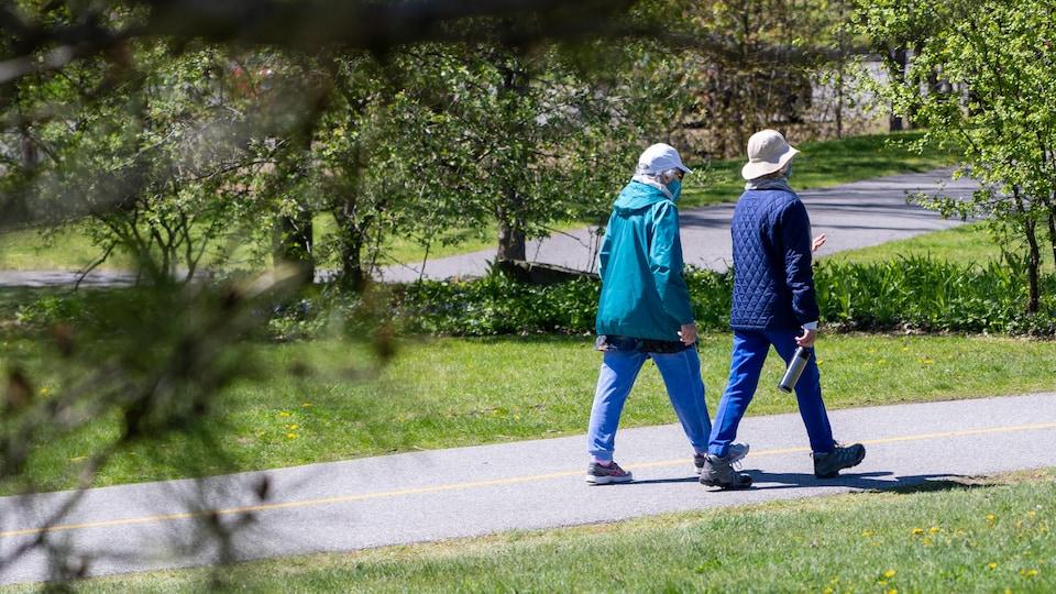 Deux personnes marchent sur une piste cyclable avec un masque au visage.