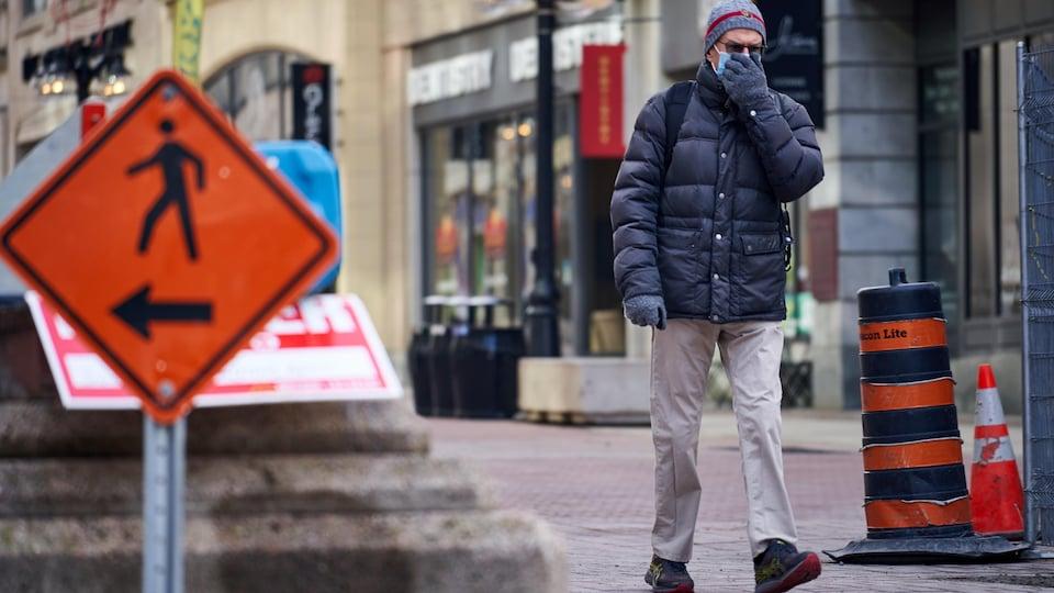 Un homme marche dans la rue avec un masque.