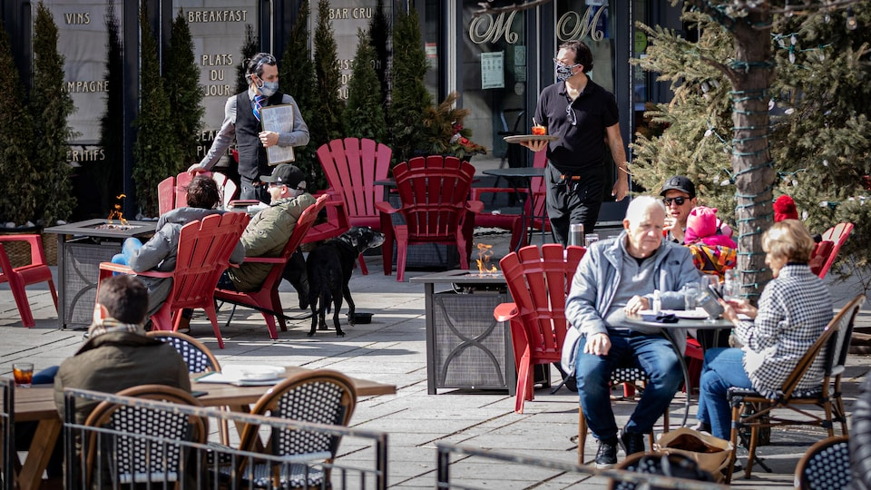 Des gens prennent un verre sur une terrasse extérieure du centre-ville d'Ottawa.
