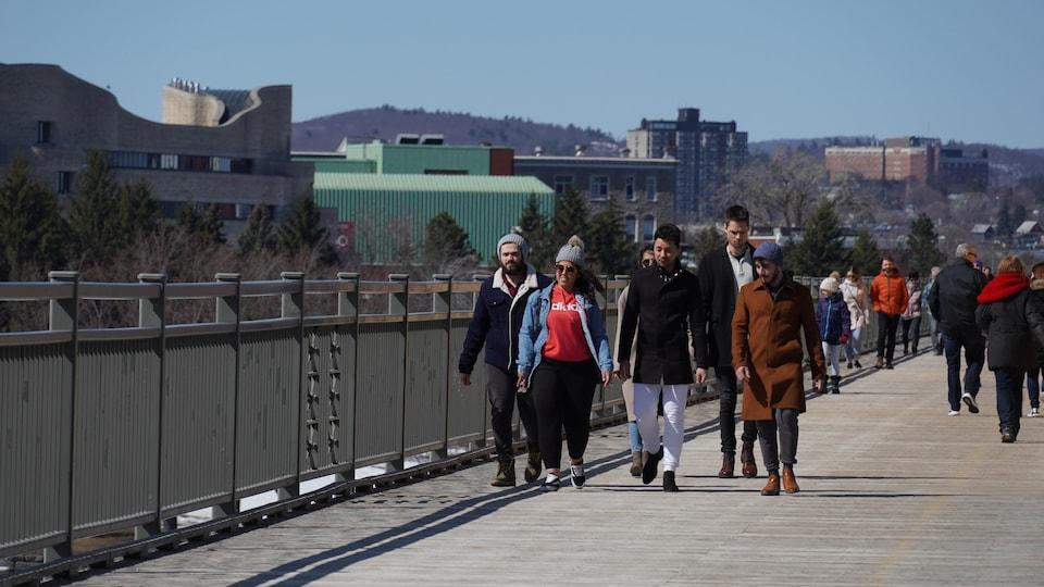 Des gens traverse un pont à la marche en petit groupe.