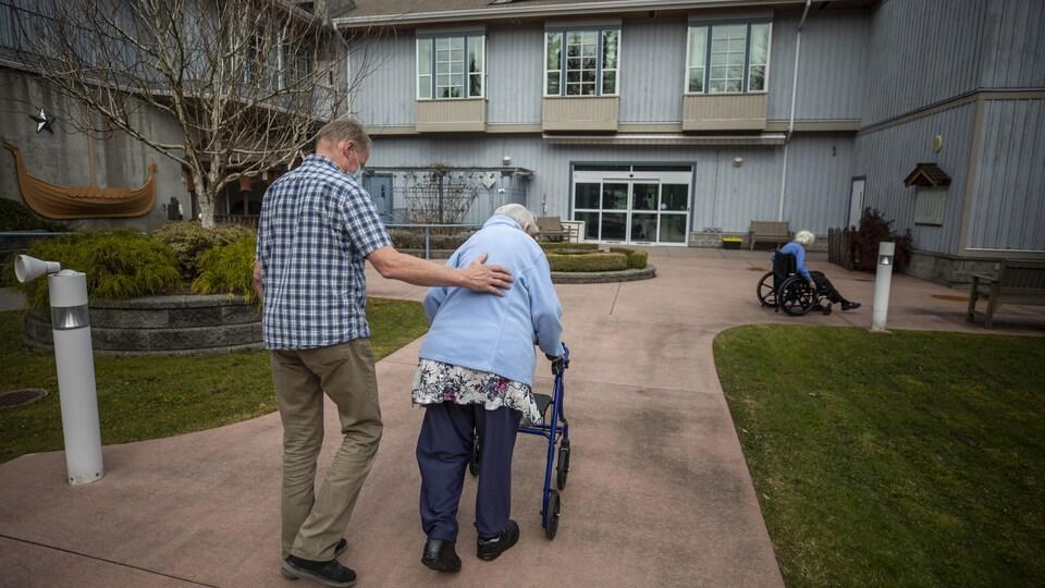 Un homme marche aux côtés d'une dame âgée qui utilise un déambulateur.