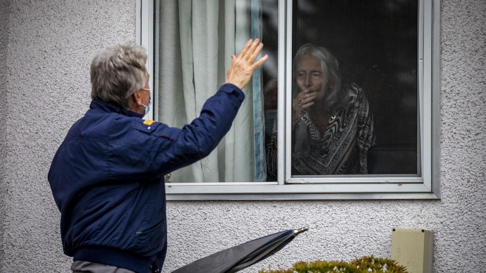 John Wilvers visite sa mère Elizabeth Jeppesen, 94 ans, à travers une fenêtre.