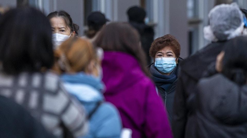 Des travailleurs de la santé avec des masques attendent en ligne à Vancouver le 22 décembre 2020.