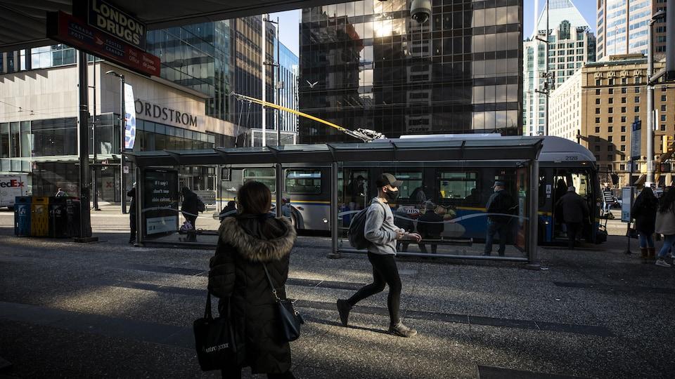 Des gens marchent et d'autres montent à bord d'un autobus sur la rue Granville à Vancouver.