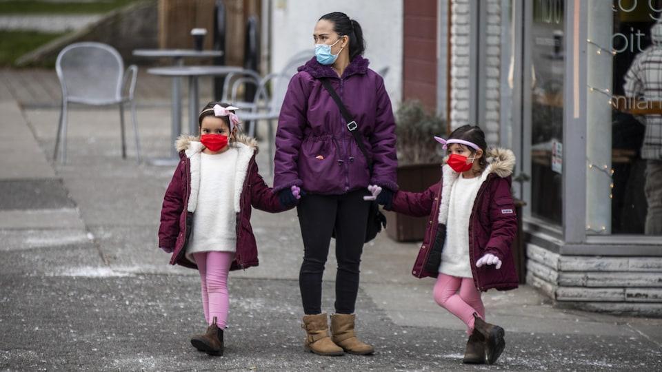 Une femme et deux enfants portant des masques.
