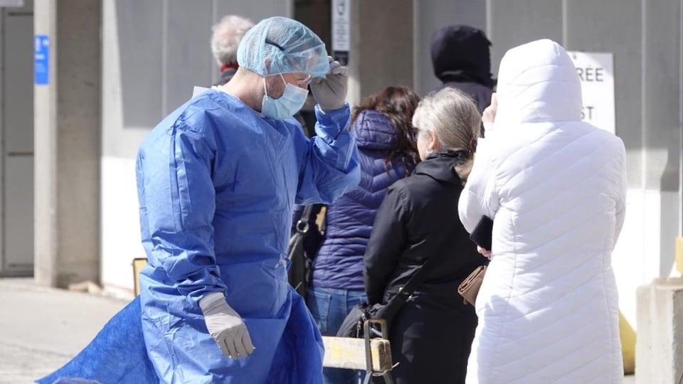 Un professionnel de la santé vêtu d'un équipement de protection s'adresse à une personne dans la file d'attente.