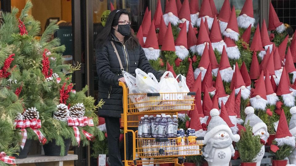 Une cliente sort de l'épicerie avec un panier rempli de provisions.