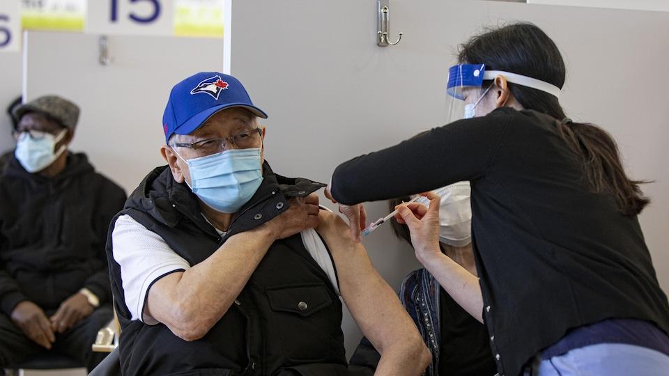 Un homme se fait injecter le vaccin dans l'épaule.