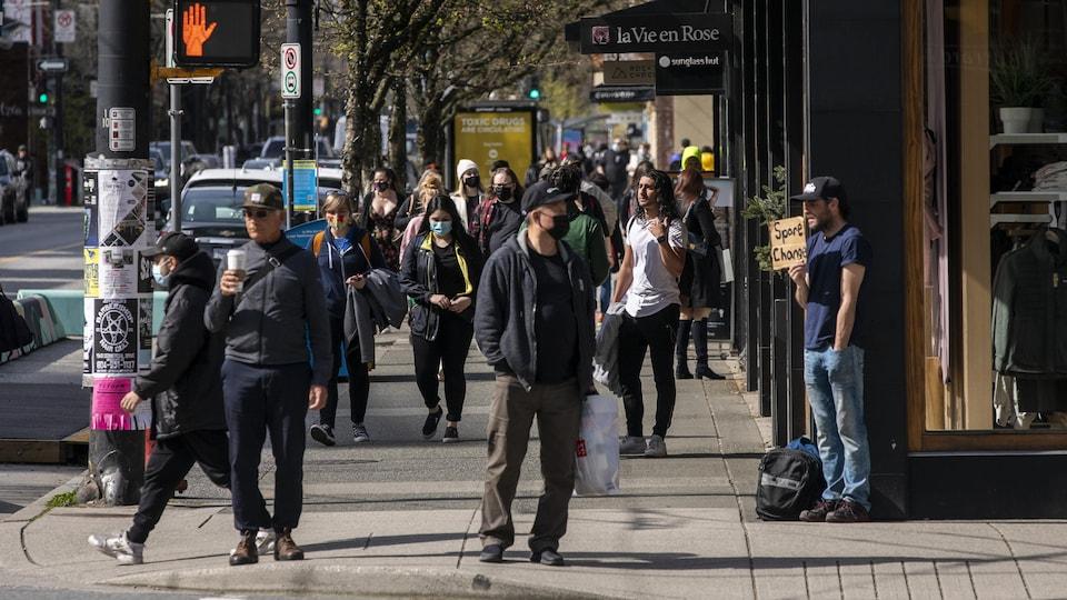 Des gens marchent sur le trottoir d'une rue du centre-ville de Vancouver le 6 avril 2021.