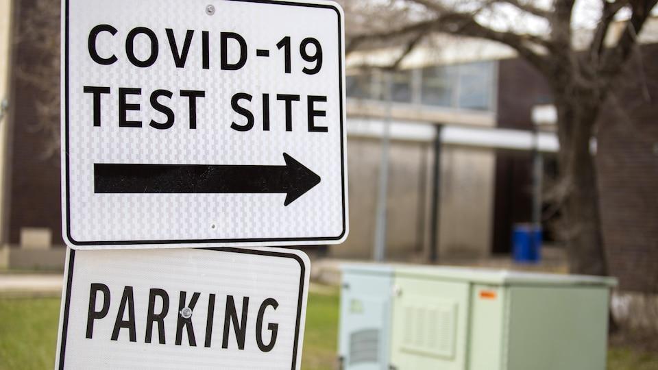 Une affiche indiquant la porte d'entrée d'un lieu de dépistage de la COVID-19.