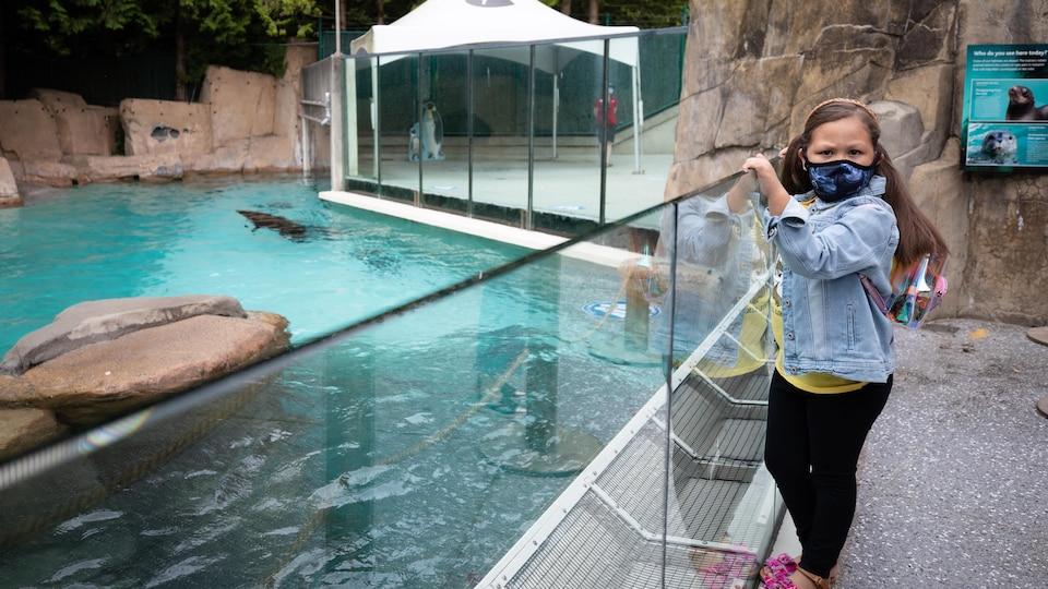 Sariah Jacobs devant un bassin où nage un dauphin.