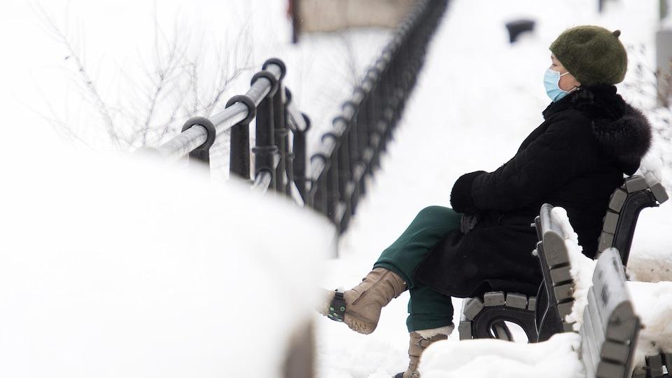 Une femme masquée est assise sur un banc. Elle est entourée de neige.