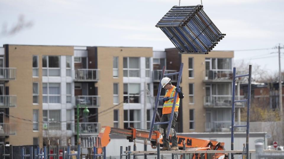 Un travailleur monte des échafaudages.