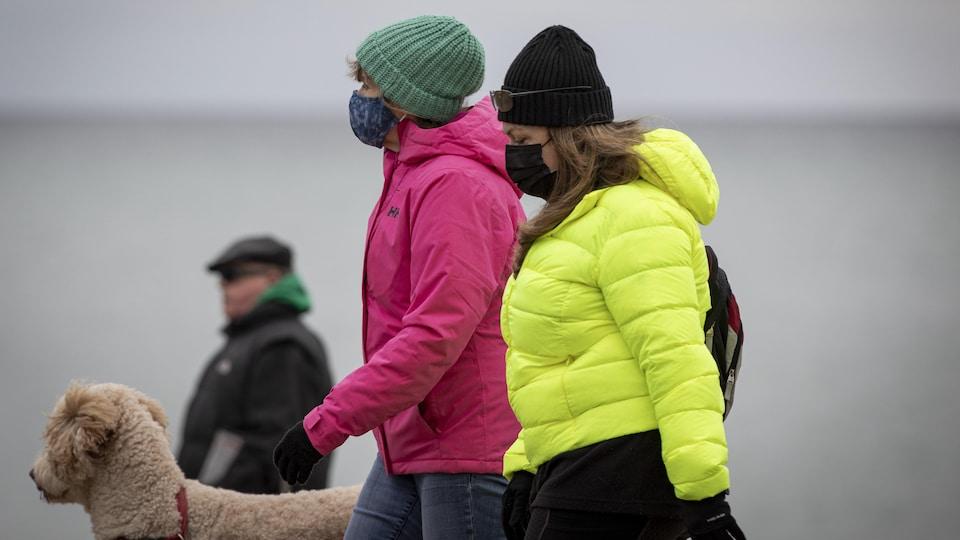 Deux femmes portant un masque promènent un chien.
