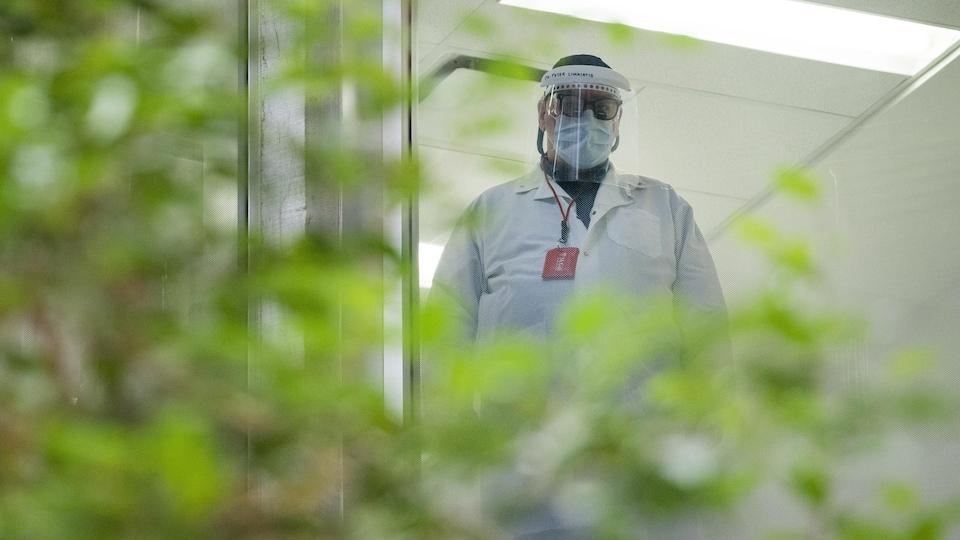 Un employé de la santé portant un masque et une visière.