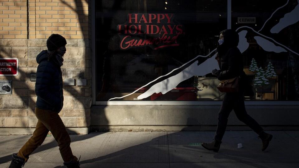 Deux passants portant des masques marchent dans les rues de Toronto devant une devanture de magasin souhaitant un bon temps des Fêtes.