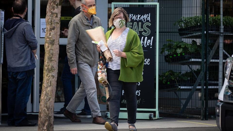 Une femme et un homme portant un masque sortent d'un magasin Whole Foods.