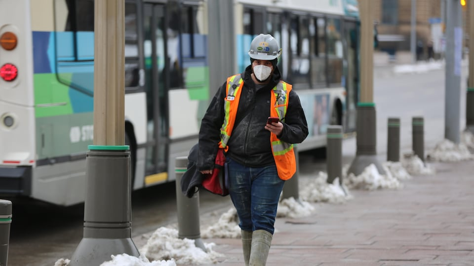 Un homme en habit de construction marche à l'extérieur avec un masque.