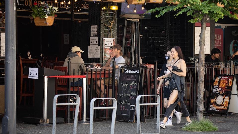 Des gens marchent sur un trottoir devant une terrasse de restaurant.