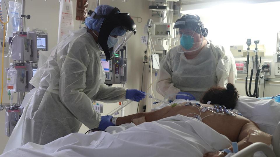 Vêtus de combinaisons sanitaires, deux membres du personnel médical prennent soin d'un patient intubé, qui est allongé sur le ventre.