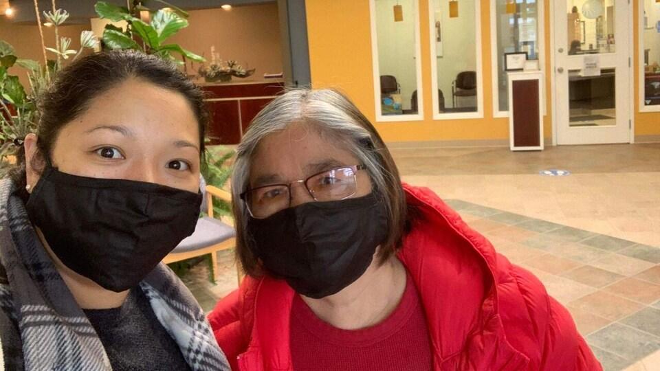 Une mère et sa fille portent le masque à l'intérieur d'un centre d'achats.