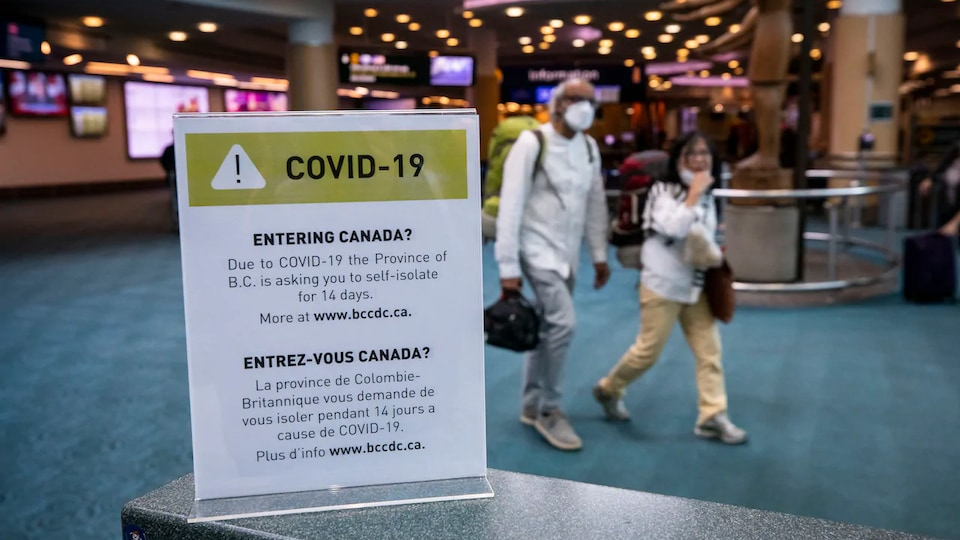 Deux passagers portant des masques marchent dans le hall d'entrée de l'Aéroport international de Vancouver au début de l'année 2020.