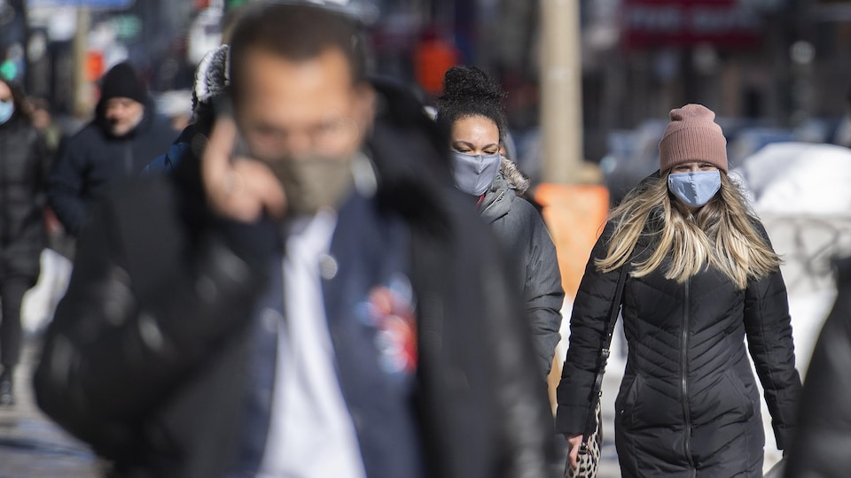 Des passants portent des masques à Montréal.