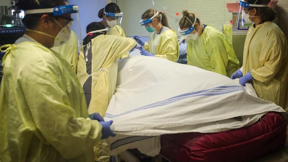 Du personnel hospitalier autour d'un lit où un patient est allongé recouvert d'un drap.