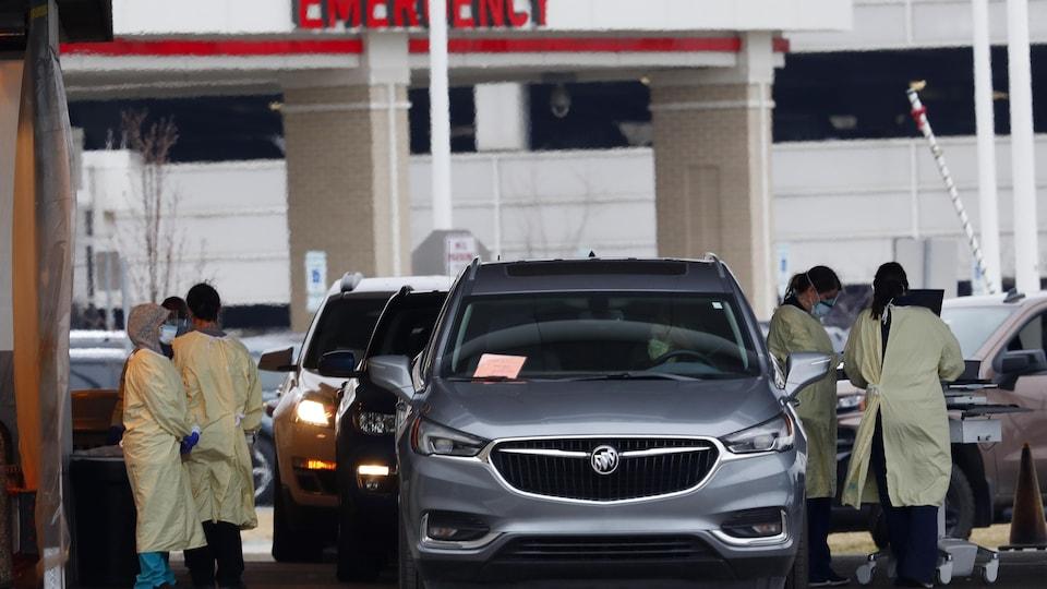 Les patients, qui arrivent à l'hôpital en auto, sont accueillis par des infirmières.