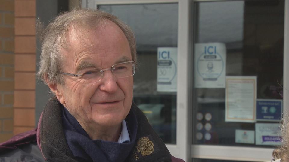 Un homme est debout à l'extérieur d'une clinique médicale, vêtu d'un manteau d'hiver.