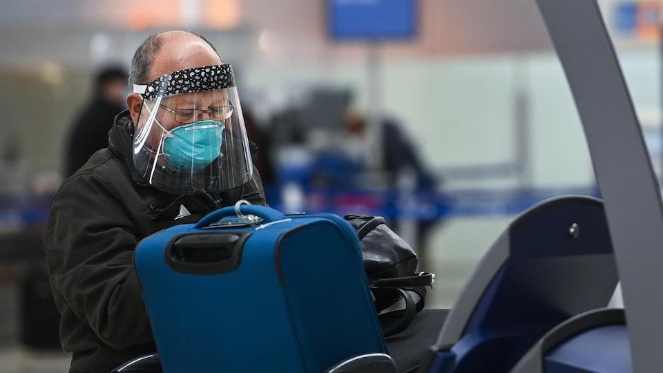 Un voyageur portant un masque et une visière enregistre ses valises à l'aéroport Pearson.