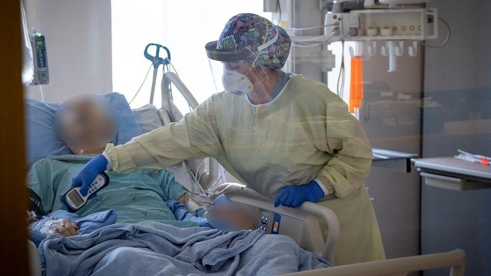 Une infirmière portant masque et visière prend les signes vitaux d'un patient dans un lit d'hôpital.