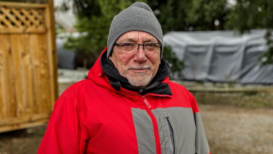 Un homme portant un bonnet sourit.