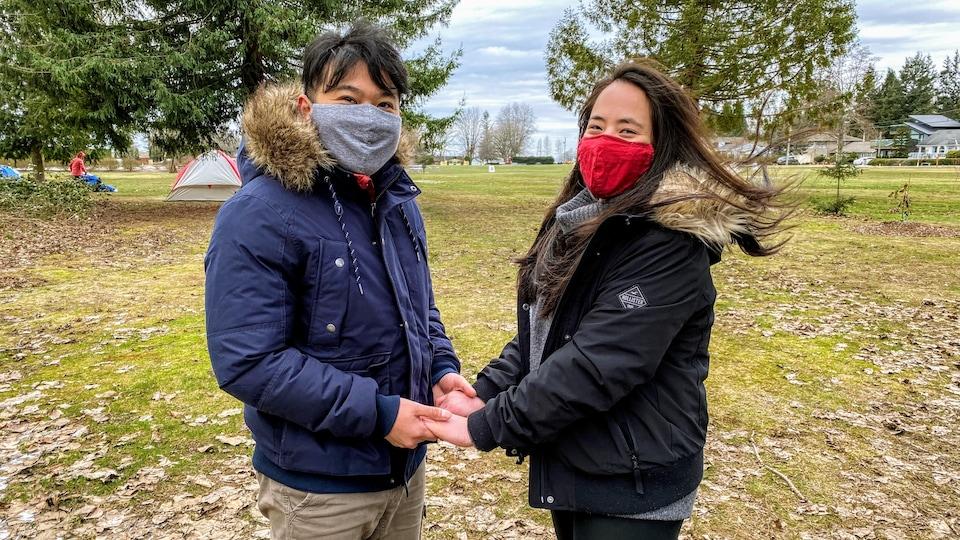 Un jeune homme et jeune femme, tous deux portant des masques, se tiennent les mains.