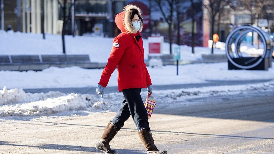 Une femme marche dans la rue avec un masque et des bottes.