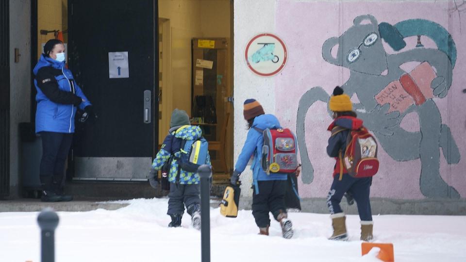 Des enfants entrent à l'école.