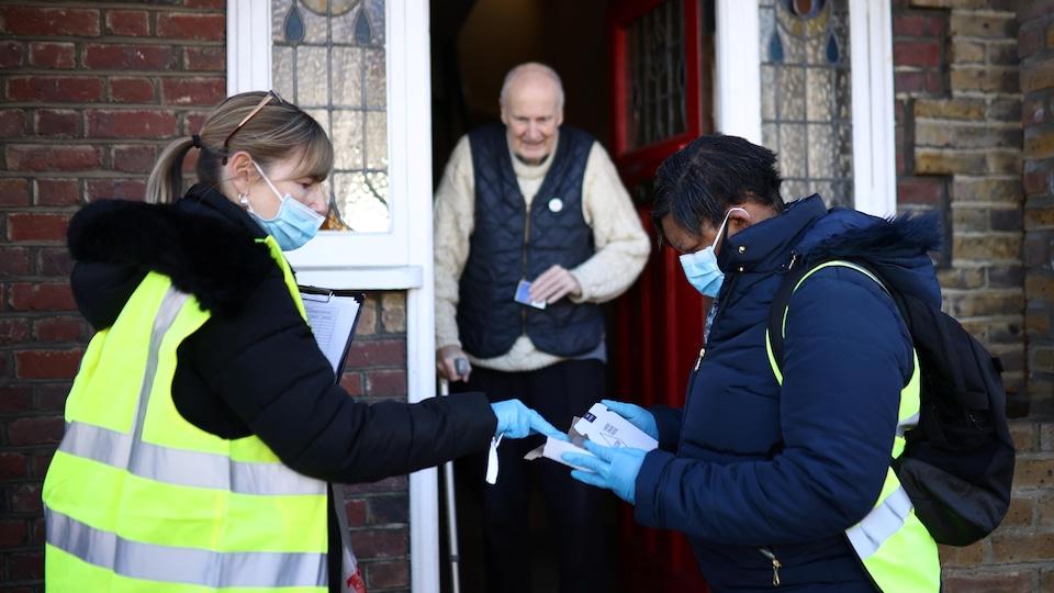Un homme et une femme masqués parlent à un homme âgé devant sa porte.