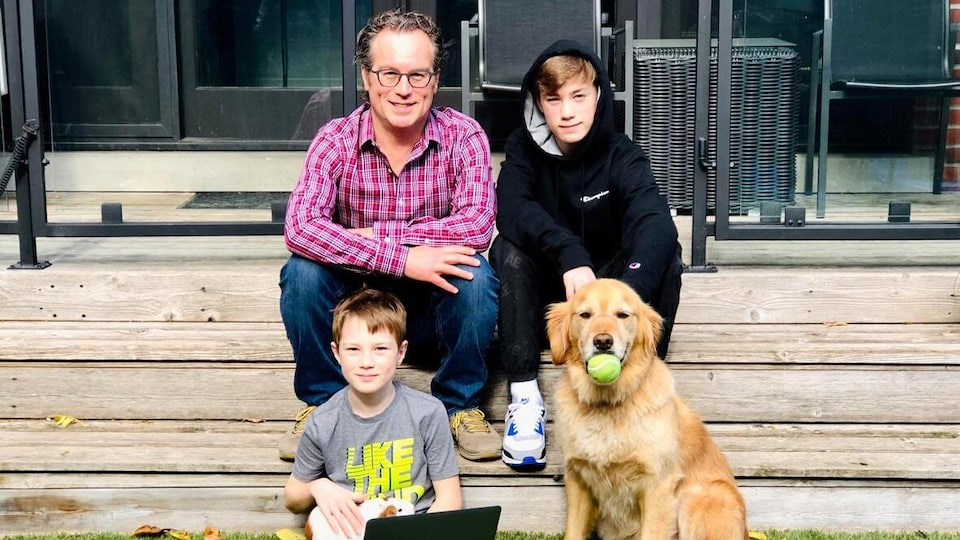 Vince Gerrie, ses deux garçons et leur chien dans les marches de leur maison.
