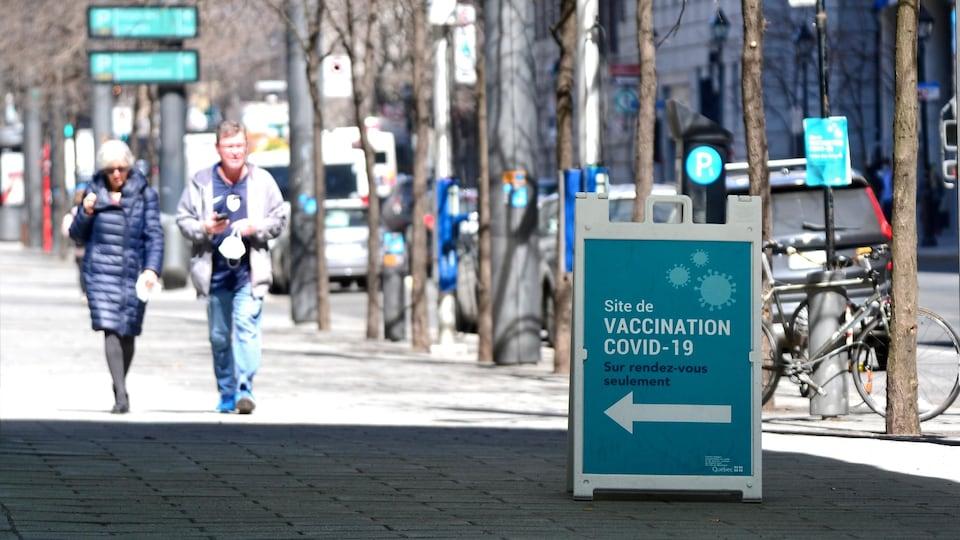 Des gens passent près d'une affiche indiquant un centre de vaccination.